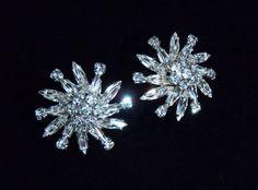 "Stunning 1960's Sherman clip earrings.  Swarovski white rhinestone asymmetrical snowflake sprays which sparkle like no tomorrow.  Diameter measures 1 14"" with a depth of 3/8""."