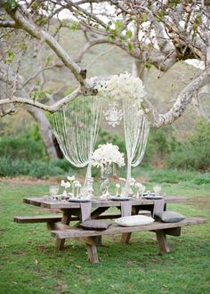 rustic backyard wedding decoration table and benches made of gray wood with pillows and napkins white flowers and elegant garlands julie hanan design Glamorous Wedding, Dream Wedding, Elegant Wedding, Glamping Weddings, Picnic Weddings, Wedding Picnic, Table Wedding, Wedding Receptions, Backyard Wedding Decorations