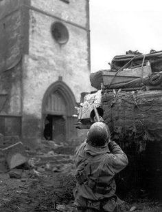 An American from B/68th Armored Infantry Battalion engages German snipers entrenched in the Church spire at Oberhoffen while the tank in the foreground provides supporting fire February 1945