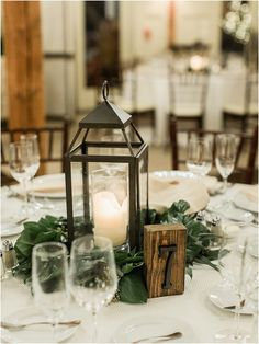 Simple winter wedding reception table with crystal and white flatware decorated with metal lanterns surrounded by magnolia leaf and greenery candle wreaths. Table numbers are simple wooden blocks with metal numbers. Barn Wedding Centerpieces, Winter Centerpieces, Wedding Reception Table Decorations, Winter Wedding Decorations, Quinceanera Centerpieces, Simple Wedding Reception, Winter Wedding Receptions, Diy Wedding, Wedding Flowers