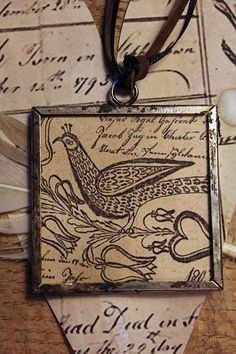 cinnamon creek dry goods......Fraktur Bird Pendant   A 2'' pendant.  Paper under glass. Double sided. Tarnished frame with short leather and ribbon hanger. Too big for a necklace, but great to hang in your home. On a cupboard knob, from a lamp, etc...                           20.00