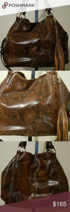 """G.I.L.I Beautiful Brown Leather Roma 2 G.I.L.I Beautiful Brown Leather Roma 2 with Snap closure. Comes with tassel, adjustable shoulder strap, NO Dust Cover. All hardware is gold toned. There are four feet on the bottom. Inside the bag there are two open pockets and a zipper compartment.  Measures approximately 20""""W x 15""""H x 1-1/4""""D with a 16"""" to 18"""" strap drop and 6"""" handles; weighs approximately 3 lbs, 8 oz. I used this bag maybe twice. It is in great condition. No wear or scuffs or…"""