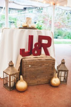Bride and groom's initials in large letters and rustic wedding décor - lanterns, gold pumpkins, wooden crate at Willowdale Estate in Topsfield, MA www.willowdaleestate.com