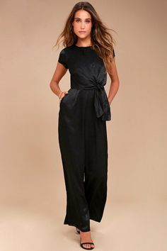 Be the perfect hostess in the Let Me Entertain You Black Satin Wide-Leg Jumpsuit! Silky satin shapes a rounded neckline, cap sleeves, and a tying waist sash that creates a chic, knotted accent. Wide-leg pants with diagonal front pockets. Hidden back zipper/clasp. #women'sjumpsuitsclassy