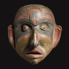 LARGE KWAKIUTL POLYCHROMED WOOD MASK    probably a depiction of Bookwus, of deeply convex form, carved with thick protruding lips, large hooked nose, deep set eye sockets, and thick arching brows, painted in red and black details, with totemic designs.  height 22 3/4 in.