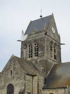 Sainte Mere Eglise, Normandy, France. We never travel into Normandy unless we make a visit here! It is so special to pray in the village church with the paratrooper stained glass window!