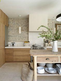 Marier la pierre, le bois et des nuances claires pour une cuisine chaleureuse et intemporelle.