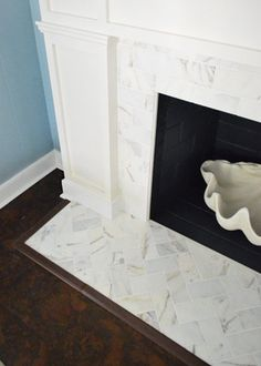 Fireplace Makeover: Young House Love Herringbone marble subway on hearth, running bond set on face.  Carrara?  Built out surround and mantle with modling details painted white.