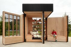 This miniature wooden library for a Toronto suburb is designed to provide a public reading nook and book exchange, and folds into a box at night for security.