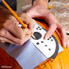 Start with a Pattern or Draw Your Own: The first step is to draw your pattern (or trace someone else's) on your pumpkin. We taped down our pattern and used carbon tracing paper to easily transfer our mask design.