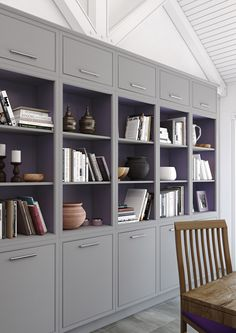 Modern classic feature bookshelf arrangement - with slim wall units, open shelves with mulberry interiors and contemporary in-frame slab doors in painted Pale Grey