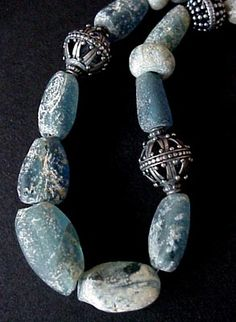 Necklace    Found along the trade route passing from Europe through northern Africa, these ancient Roman glass beads are a treasure! The beads vary in size and shape and all show the beautiful pitting from being buried in the sand for centuries. Combined with sterling Indonesian beads, this is truly a timeless piece of jewelry    Nomad's Journey Designs