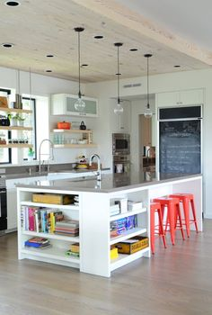 Lots of clever details in this kitchen reno - open shelving, cookbooks shelves, counter seating, wood ceiling, blackboard menu / Judy and Don's Treehouse in the City — House Tour | Apartment Therapy