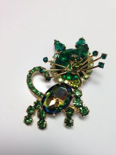 D&E aka Juliana Cat Brooch has a round faceted green stone for the head and it is outlined with aurora borealis chatons. Ears are 2 small green pear