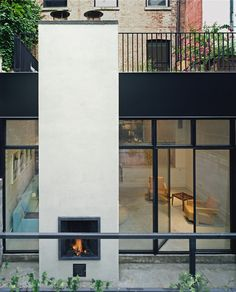 A chimney with back-to-back indoor and outdoor fireplaces anchors the steel and glass wall of the rear addition and allows the courtyard to be used well into autumn as an extension of the living space. Running the same troweled concrete flooring inside and out reinforces this idea.