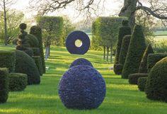 double row of giant topiary, sculpture art in between