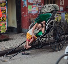 A hand rickshaw parked on the roadside being temporarily used as a recliner. What is the first piece of mathematics that you see in this picture?
