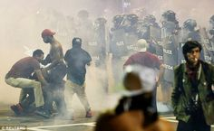 People struggle amongst tear gas in uptown Charlotte during a protest of the police shooting of (Armed) Keith Scott (by a Black Officer.)