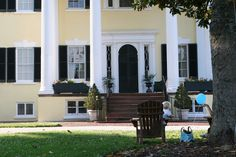 A mother and child rest in the shade in front of the Oatlands Plantation mansion.