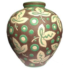 Charles Catteau for Boch Freres vase with rough-textured background, decorated with glazed stylized leaves and abstract circles. Belgium, 1930.
