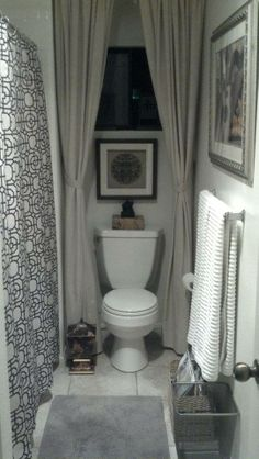 This is how I turned the toilet into the throne. Inexpensive cotton curtains from Ikea, safety pins and a tension rod were used to get this look that also hides the plunger and the toilet brush.