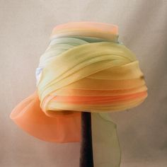 The front of previous hat. Ethereal Elsa Schiaparelli netted turban with sassy bow (front view) | This hat features multiple layers of pleated tulle in beautiful pastel shades of green, yellow, pink and blue | An enormous bow protrudes from one side, making the hat a real show-stopper #millinery #judithm #hats