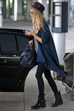 Le Fashion Blog -- Airport Look: Clemence Poesy -- Parisian Casual In A Feather Red Hat, Teal Blue Draped Cardigan, Duffle Satchel Bag, Leggings & Buckle Moto Boots -- photo Le-Fashion-Blog-Airport-Look-Clemence-Poesy-Parisian-Casual-Feather-Red-Hat-Drape-Cardigan-Leggings-Buckle-Moto-Boots.jpg
