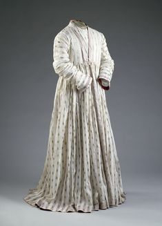 Man's robe (Jama) of white cotton muslin embroidered with gold. Woven in vertical stripes, alternately clear and opaque. The clear stripes are patterned at regular intervals with sprigs of gold foil, applied to the face of the material and stitched down on the reverse with white thread. The hem, collar, cuffs and other borders are faced on the inside with red satin. Late 18th century. Said to belong to Tipu Sultan.