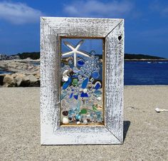 7 w x 11Shooting sugar or white finger star fish . lots of cobalt blue accented with NE seashells in white wash frame. The materials are not glued