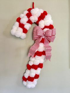 This Candy Cane Pom Pom Wreath adds a modern touch to a classic Christmas decoration. The wreath is made up of over 75 handmade red and white yarn Pom poms and a handmade red and white striped glitter bow. This wreath looks amazing hanging on covered doors, walls, and mantels. It
