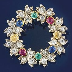 An Edwardian diamond and gem garland brooch  The openwork garland with diamond three stone flowerheads and claw-set vari-coloured gem spacers including: emerald, ruby and sapphire, circa 1905