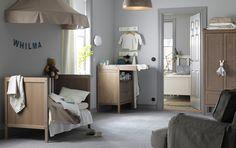 Dormitorio infantil con una cuna de color marrón grisáceo transformada en cama y con dosel, un armario, y un cambiador también de color marrón-grisáceo.
