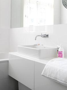 Bright white bathroom with bath, sink and mirror