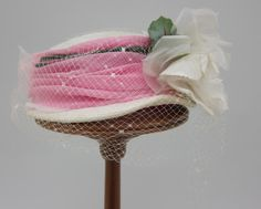 Hat of white straw trimmed with chiffon, net and a flower | United States, 1952-1957 | Label: Coralie | The hat is formed as a modified pillbox, with cylindrical white straw crown, very slightly domed | Around the crown is a wide band of ruched pink chiffon overlaid by white netting/veiling. At front is a large artificial silk flower | University of North Texas