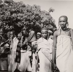 Nigeria, medium group of female adults and children standing outdoors. Wearing cloths around upper and lower bodies and heads. Two females at right have plaited and beaded hair-styles. Tree in background. Medium: Gelatin silver print.