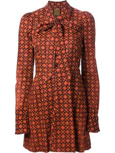 Orange and black cotton geometric print mini dress from Biba featuring a pointed collar, a pussy bow fastening, long sleeves, button cuffs and a back inverted pleat. farfetch.com.