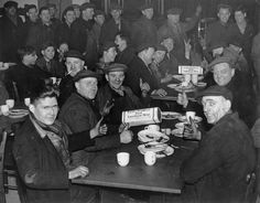 Dock workers give the thumbs up and V signs as they lunch on American canned meat at a London Dockworkers Canteen, London, 1941.