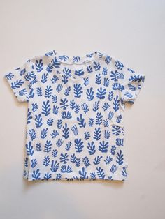 Introducing the Matisse Inspired T-shirt! This super soft t-shirt is made from 100% organic cotton. It is made to grow and move with your child. This is a white t-shirt with a blue cut-outs print. It is available in 12 M - 4 T. All Ollie + Squish fabrics are sourced within the US with