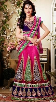 Famous designers tend to give reign to their imagination and create clothes that look interesting and guided by the desire to attract attention in this pink/purple net embellished lehenga cholie. Lehenga features floral multi colored resham embroidered motifs with similar contrast appliqued embellished broad border in the flare. #WeddingLehengaCholi