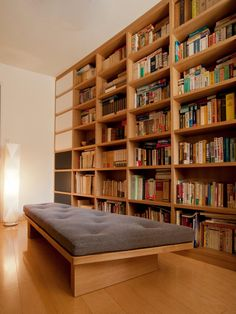 台形の部屋に合わせて製作した 大容量の本棚。  一列を扉付きの収納にしています。  扉は、ホワイトとネイビーに色分けされたMDFのエナメル塗装。  本体に使用したナラ材とエナメル塗装のコントラストが、 よりいっそう、お互いの素材の良さを引き立てています。  中央のベンチは、部屋の形に合わせたデザインで 動線とゆったりくつろげるスペースを考えた上でのデザインです。    (価格は、設置費、配送費込み)