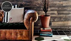 stacked books, an old leather sofa that's had to have its cushion replaced by velvet, pallet walls.....much to love here