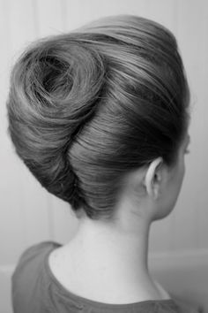 Updo with hair twisted into a large victory roll at the back and a small bouffant at the front
