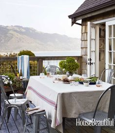 """The setting is the star,"" says Dempster, who kept the outdoor dining area simple. An assortment of galvanized metal furniture — including Crate & Barrel's Lyle chairs and 1934 Dining Chairs from the Sundance Catalog — are gathered around a table covered in Sundance's Americana tablecloth, made of homespun cotton and linen. Alec Hemer  - HouseBeautiful.com"