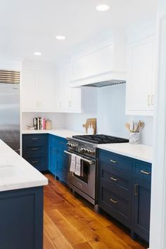 White and navy blue kitchen features white upper cabinets and navy lower cabinets painted Benjamin ...