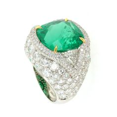 The ultimate cocktail ring, this 9.66 carat natural cushion cut emerald is surrounded by 6.94 carats of diamonds set in platinum. Sparkling from any angle, this bold ring makes quite a statement.