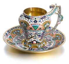 A silver-gilt and cloisonné enamel tea cup and saucer, Adrian Ivanov, Moscow, 1908-1917, the cup of baluster form with scroll handle, the surfaces enamelled with shaded floral and geometric motifs on polychrome grounds, cloison borders.