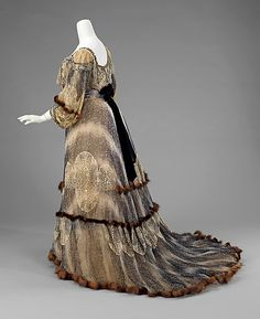 Fur-trimmed silk evening dress (back), by Raudnitz and Co. - Huet and Chéruit, French, 1895-1900. With a label from the French house of Huet & Cheruit, this gown serves as a virtuoso example of couture garment in its combination of materials and overall visual effect. The print of the textile is meant to look like fur, probably chinchilla. Combining the print with real fur trim heightens the trompe l'oeil effect, as well as adding texture and an additional level of luxury to the design.