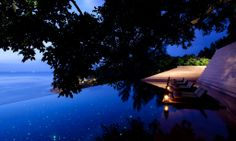 Paresa  :  Phuket, Thailand.  The Miracle Lawn - or infinity pool where guests can dine seated on 'private islands' in the fibre optic-lt infinity pool.