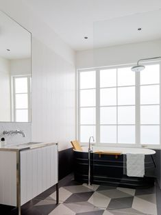 In this bathroom, a steel bath sits on an Escher inspired tile pattern. It also features a nickel plated brass mirror frame and vanity structure, infilled with timber paneling, reflecting elements found throughout the house, as well as being topped with a light Carrara marble top and backsplash.