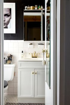 Black and white bathroom with fashion art and mirrored cabinet